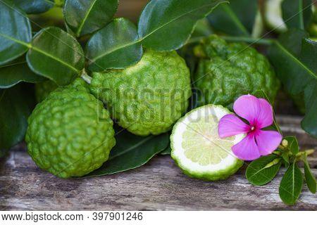 Fresh Bergamot Fruit And Pink Flower, Kaffir Lime, Citrus Bergamia With Leaf On Wooden Table, Slice