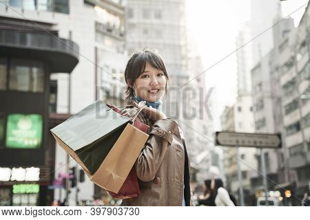 Happy Young Asian Woman Carrying Shopping Bags Walking On City Street