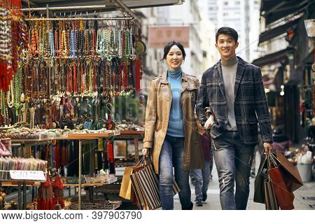 Young Asian Couple Walking Through A Street Commodity Market Carrying Shopping Bags