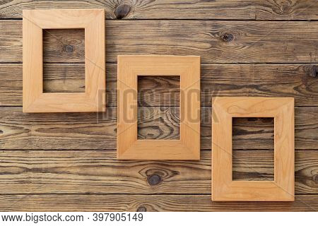 Three Wooden Frame Or Photo Frame Over Wooden Background, Copy Space, Design And Home Interior.