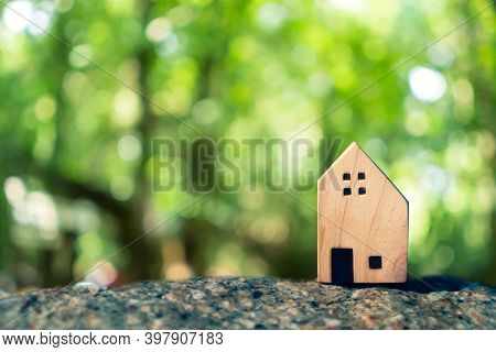 Closed Up Tiny Home Model On Floor Or Wood Board With Sunlight Green Bokeh Background. Deam Life Hav