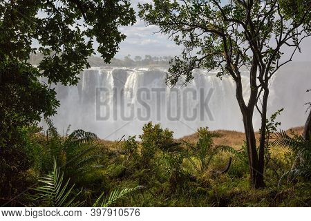 Victoria Falls From Zimbabwe. View From The Rainforest. In The Background Blue Sky And White Clouds