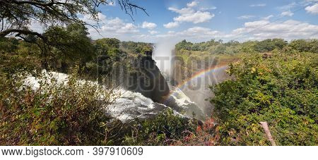 Swirling Zambezi River. Victoria Falls. Rainbow On A Background Of Blue Sky With White Clouds.