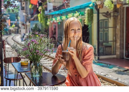 Young Woman Traveler Drinks Coffee Sitting By The Railway Paths Which Go Through Residential Area In