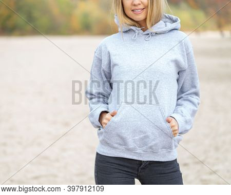 The front view of unrecognizable woman wearing light grey hoodie. She stands on the beach. Copy space on empty area on her blouse for design or inscription. Fashion mockup.