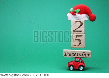 Russia, Vladivostok, December 4, 2020: A Small Red Toy Car Carrying December 25 On Wooden Blocks And