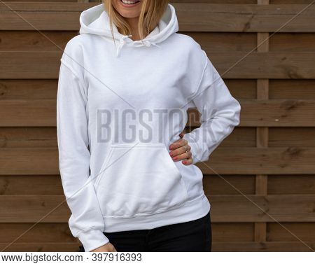 Blond unrecognizable woman wears white hoodie, she stands in front of camera. The empty space on her blouse in for design or inscription, for clothing mockup.