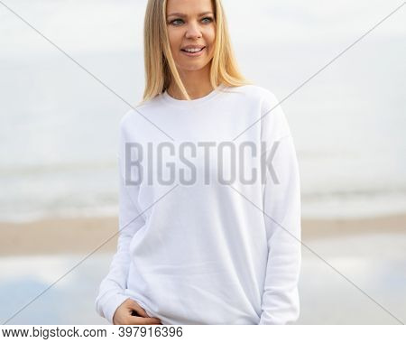 Fashion mockup with copy space. Smiling blond woman stands in white blouse in front of camera. Outdoor view on beach.