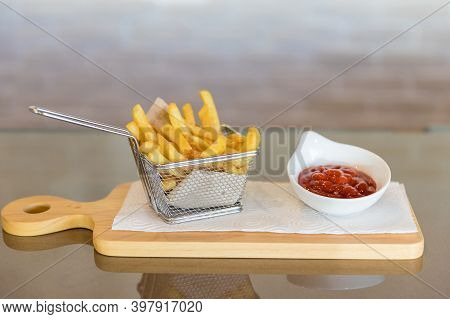 Fried French Fries On A Basket On The Wooden Cutting Board. Yummy French Fries As Background. French