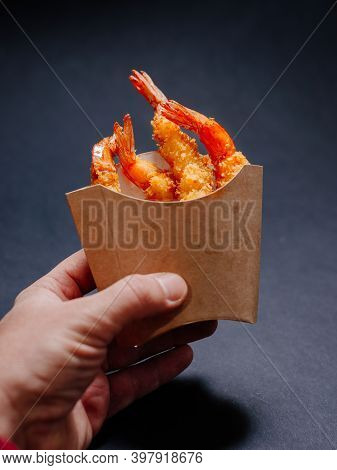 Male Hand Holding Paper Box Without Logo With Tempura Shrimp. Fried Tempura Shrimps In A Paper Box W