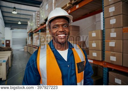 Smiling Portrait Of A African Young Male Worker In White Hardhat And Uniform At Warehouse