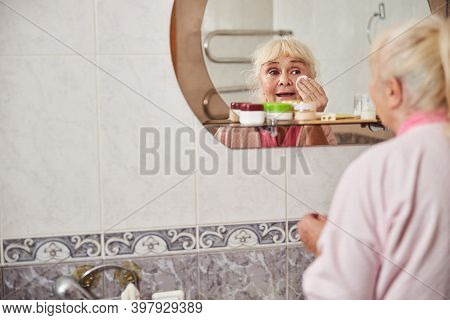 Lovely Old Woman Cleaning Face With Cotton Pads In Bathroom