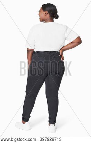 Plus size women's white tee and jeans fashion studio shot