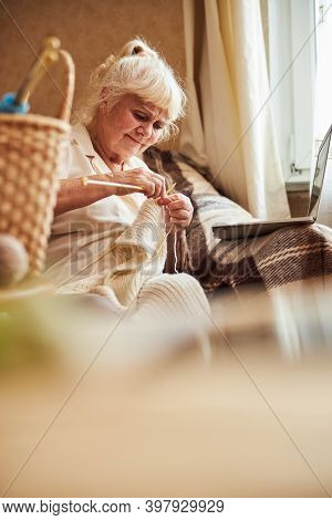 Nice Old Woman Knitting And Using Notebook At Home
