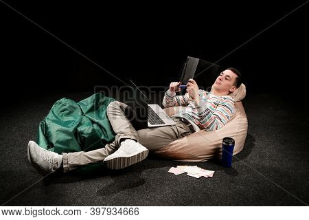A Man On Self-isolation During Quarantine, A Man In Bright Clothes Lies On A Pouf And Looks Into A G