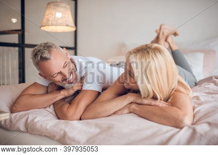 Grey-haired Man And A Blonde Woman Lying On The Bed And Looking At Each Other