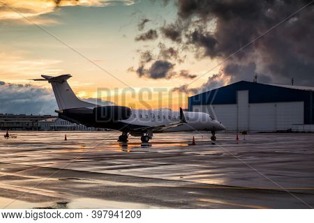 Business Jet At Sunset After The Rain On The Airport Apron Near The Hangar