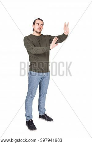 Full Length Of Cautious Man Showing Stop Gesture With His Palms, Arms Outstretched As Deny Or Refuse