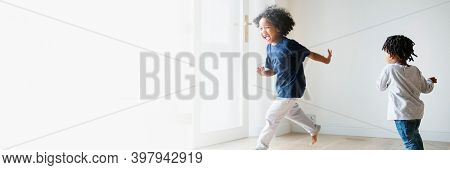 Two black kids playing and chasing each other in an empty room text space
