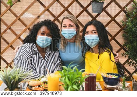 Multiracial Friends Wearing Face Mask While Having Healthy Lunch In Coffee Brunch Bar During Corona