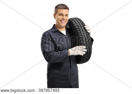 Auto mechanic worker carrying car tire on shoulder and smiling at camera isolated on white background