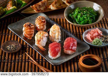 Sushi Set Nigiri, Gyozas Dumplings And Wakame Salad In Ceramic Plates With Soy Sauce And Chopsticks