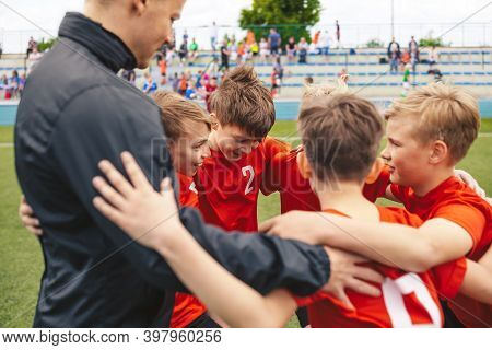 Happy Boys In Sports Team Huddling With Young Coach. Kids Standing In A Circle On Grass Sports Pitch