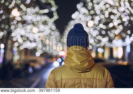 Christmas Holiday In City. Rear View Of Young Man Against Illuminated Street With Shops. Prague, Cze
