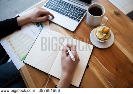 Hands Using Laptop And Notebook With Cup Of Tea And Cake On Wooden Table In Cafe