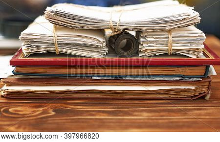 Albums With Old Family Photos, Photos Tied In A Stack On A Wooden Table. Home Photo Archive.