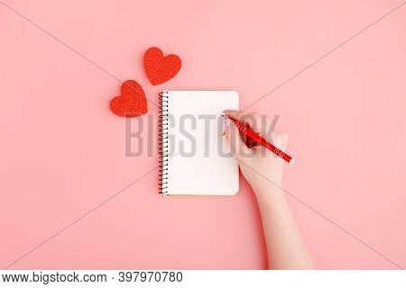 Woman Hand Writes Message On White Notepad, Two Hearts Isolated On Pink Pastel Background Top View,
