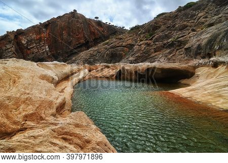 Mountain Nature Pool Amongst Rocks On Background Of The Mountains And Endemic Trees, Socotra, Yemen