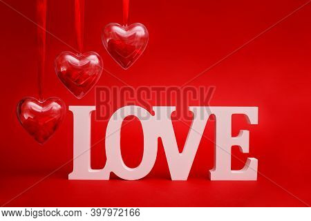 Transparent Heart With Red Confetti Inside With Wooden Letters Word Love On Red Background. Valentin