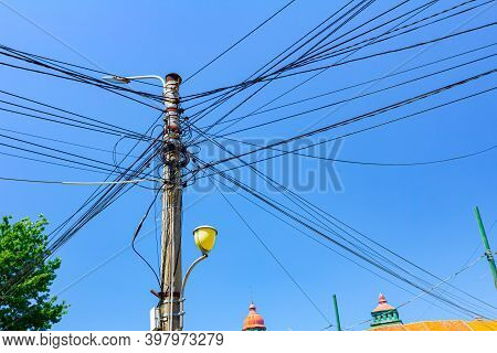 Tall Power Line Street Lamppost In The City With A Lot Of Wires, Blue Clear Sky Is Above.