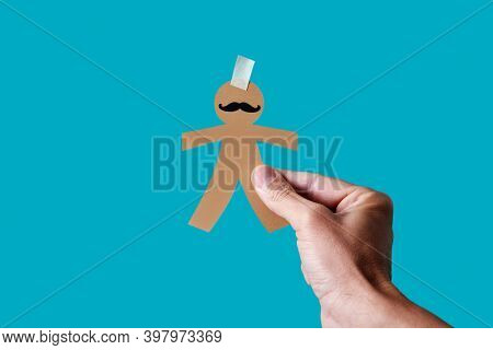 man with a paper man doll in his hand, as a prank for dia de los inocentes, the innocents day, a feast held in spain, hispanic america and philippines equivalent to april fools day, blue background
