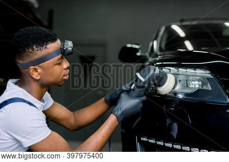 Detailing And Polishing Of Car Headlight. Young Dark Skinned Worker In Uniform And Protective Gloves