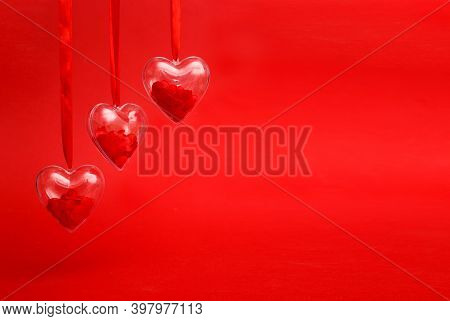 Transparent Hearts With Red Confetti Inside On Red Background. Valentines Day Greeting Card Concept.