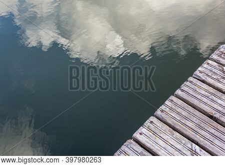 Pier In The River With Reflections In The Water, Top View. Clouds Are Reflected In The Water. Backgr