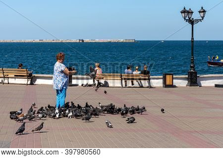 A Woman Feeds Pigeons On The Sevastopol Embankment With People On August 13, 2020. Tourist Center Of