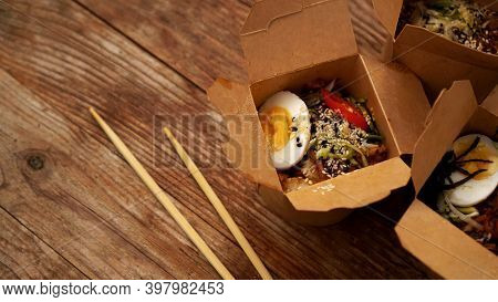 Chinese Noodles With Chicken And Vegetables In Cardboard Boxes On A Wooden Background, Asian Food De