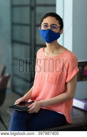 Mixed race woman wearing face mask in an office. sitting, looking at the camera and using digital tablet. hygiene in workplace during coronavirus covid 19 pandemic.