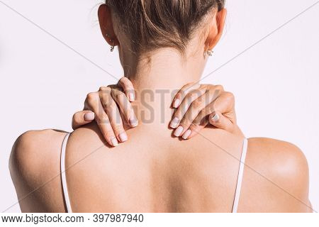 Closeup Shot Of Woman From Back Having Neck Or Shoulder Pain. Injury Or Muscle Spasm. Back And Spine