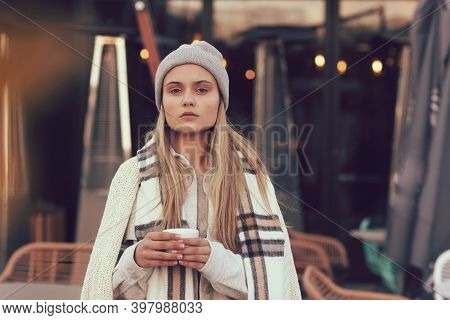 Blond Lgirl In Knitted Hat And Scarf With Coffee Paper Glass Close Up Portrait In Cafe