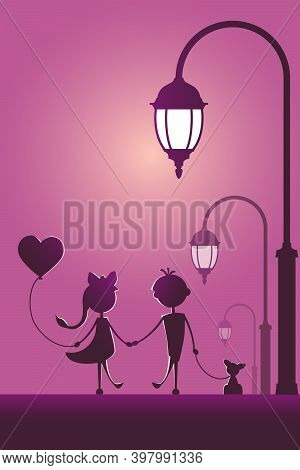 Silhouettes Of A Boy And A Girl Walking In The Street Light.