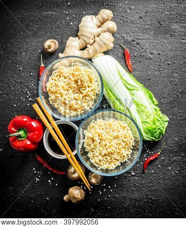 Instant Noodles With Ginger, Mushrooms, Bell Peppers, Peking Cabbage And Soy Sauce. On Black Rustic