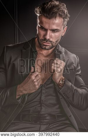 Handsome Stylish Sexy Man In Elegant Suit, Posing On Dark Black Background.
