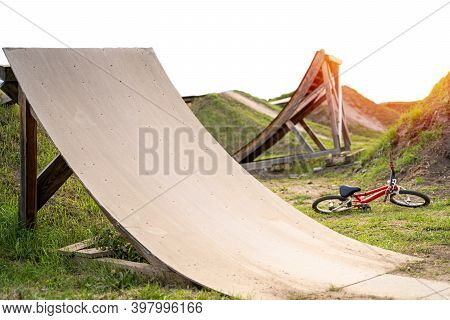 Bmx Springboard Made Of Wood Near Laying Red Bike On Sunset