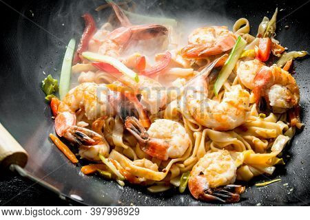 Chinese Wok. Hot Udon Noodles With Shrimp, Sauce And Vegetables. On Rustic Background