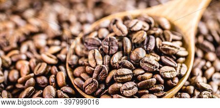 Rustic Wooden Spoon With Roasted Arabica Coffee Beans, Scattered On The Table. Cappuccino Coffee Pre