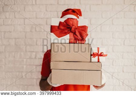 Young Funny Delivery Man In Santa Hat, Protective Gloves Hide Behind Cardboard Gift Boxes With Red B